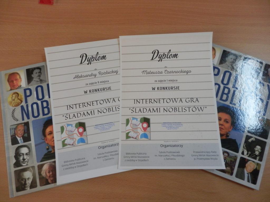 """zdjęcie przedstawiające dyplomy i nagrody książkowe """"Polscy Nobliści"""" laureatów konkursu Internetowa Gra """"Śladami Noblistów"""""""