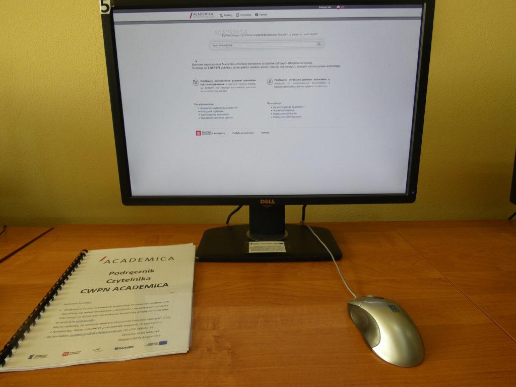 Na zdjęciu biurko na którym stoi komputer z uruchomioną przeglądarką academici na biurku leży po lewej stronie Podręcznik obsługi academici
